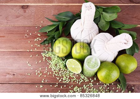 Spa composition with lime and compress balls on wooden table background