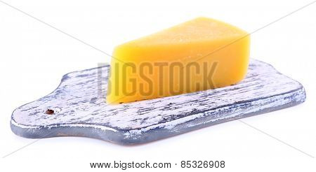 Chunk of Parmesan cheese on wooden cutting board isolated on white