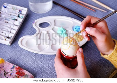 Painting Easter eggs by female hands on colorful tablecloth background