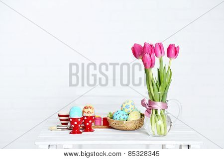 Table with flowers, decorated Easter eggs and brushes, on light background