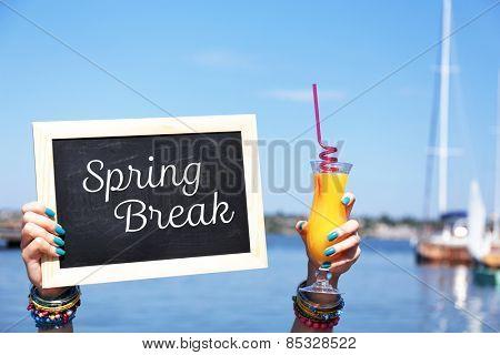 Spring break concept. Chalkboard in female hands on beach background