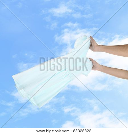 Hands holding flying dress on sky background
