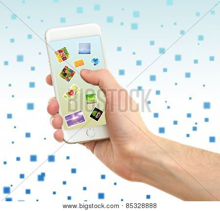 Touch screen mobile phone with beautiful images on light abstract background