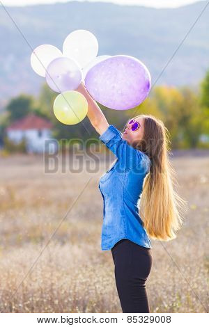 Girl playing with bunch of balloons outside