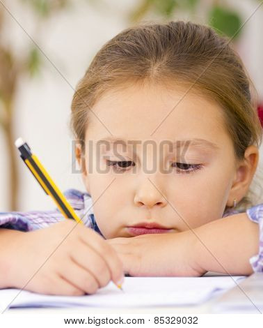 Portrait of child writing homework at domestic room