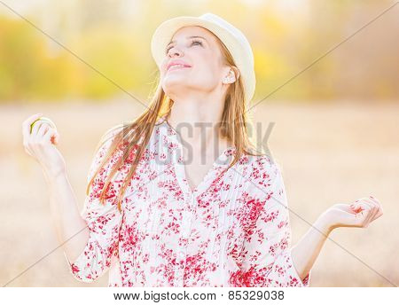 Young girl with hat enjoying in beautiful day in nature