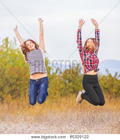 Two girlfriends jumping together
