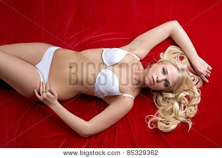 Top view of hot blonde lying on red bedsheet