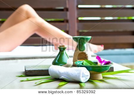 Arrangement of spa treatment products made out of massage oil and towel by poolside with pair of woman's leg in background.