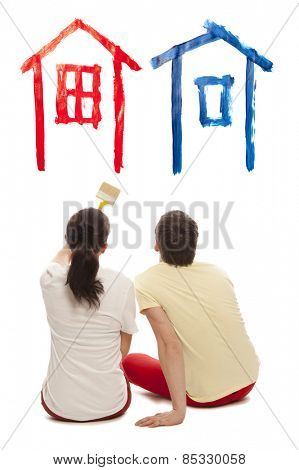 Dream house. Young caucausian couple with paint brushes together. Isolated on white background