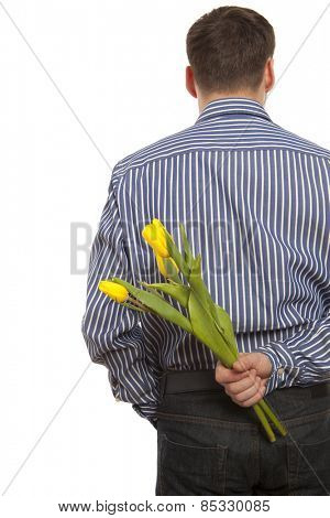 Man hiding bouquet of flowers tulip behind his back isolated on white background