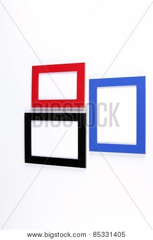 Three retro wooden photo frames, red, blue, black on white wall background.