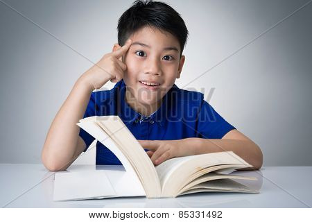 Little Asian Boy Read A Book And Think About