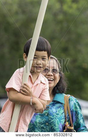 Grandmother With Kid On Swing In Playground