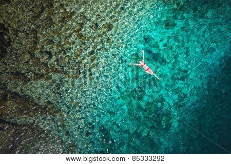 Young woman swimming in beautiful azure sea