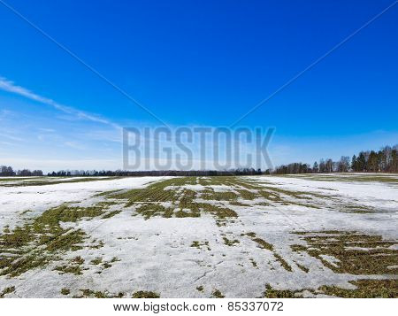 Wide field in spring with snow and thawed