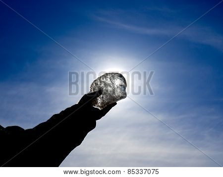 Transparent piece of ice in his hand before the sun