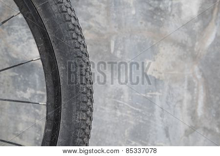 Dirty bike wheel-Concrete background.