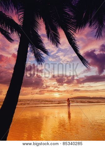 Woman taking pictures of the sunset on the beach of Ao Nang in Krabi Thailand.