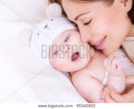 Closeup portrait of beautiful gentle mother playing with cute little baby lying down on the bed, closed eyes of pleasure, loving young family, happy motherhood concept