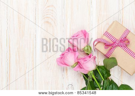 Valentines day background with pink roses over wooden table and gift box. Top view with copy space