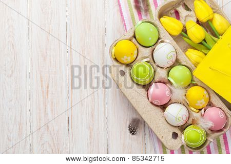 Easter with yellow tulips, colorful eggs and gift bag. Top view with copy space