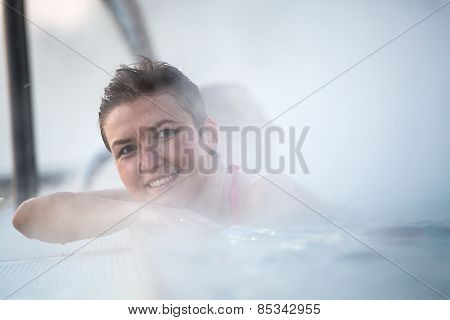 Young woman relaxing in thermal pool.