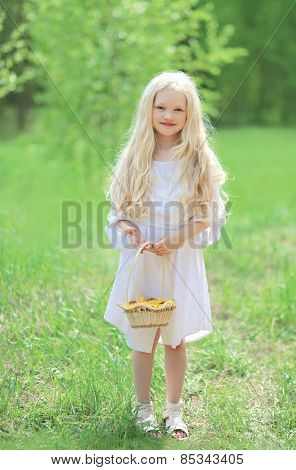 Spring Portrait Of Cute Little Girl In White Dress With Long Blonde Hair Holding A Basket Of Yellow