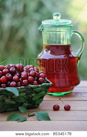 Cold Refreshing Drink From Cherries In A Pitcher And Ripe Berries In Basket On Wooden Table In The G