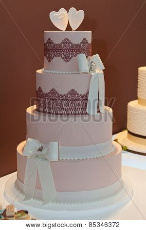Wedding cake decorated with bows and lace