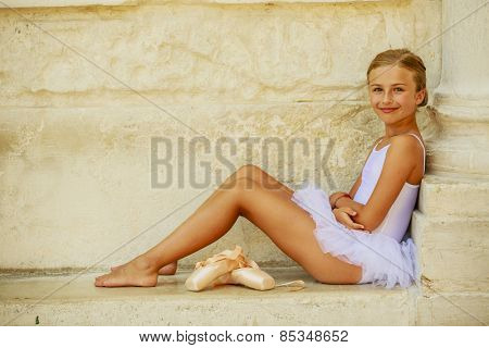 Beautiful ballet-dancer in white dress and pointe shoes dancing in Venice Italy