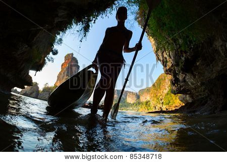 Silhouette of the young lady entering marine cave with kayak