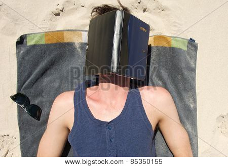 Young Man Sleeping On Beach With Book Covering Face