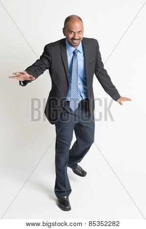 Full body Indian businessman walking balance , front view on plain background.
