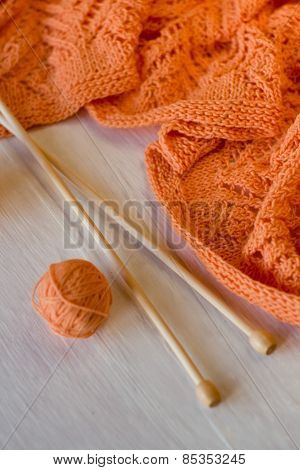 Bright Orange Plaid Knitted, Knitting Needles And Yarn Balls On A White Wooden Background