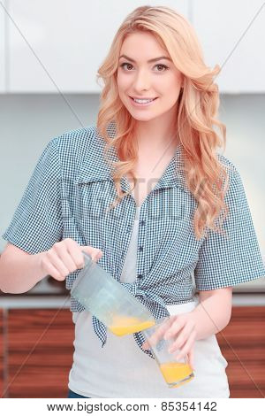 Young attractive woman making fresh juice