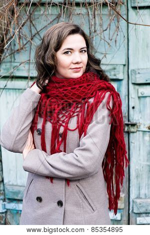 Portrait Of A Young Beautiful Curly Brunette In Beige Coat And Knitted Red Kerchief