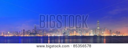 Hong Kong Victoria Harbor morning with urban skyscrapers over sea with blue tone and street light.
