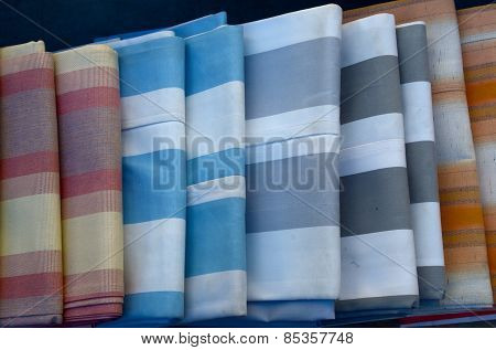 carelessly stacked striped fabric in different colors