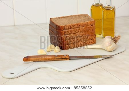 Sliced Bread,garlic And Olive Oil On Kitchen Table.