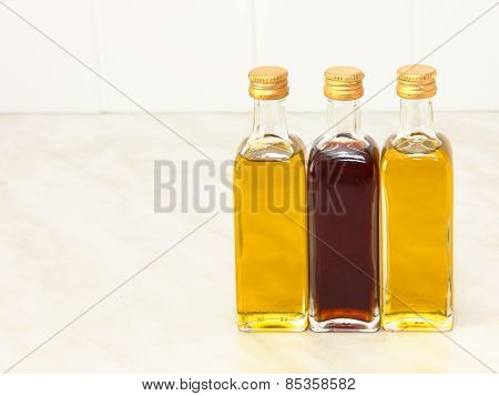 Three Vegetable Oil Bottles On White Kitchen Table.