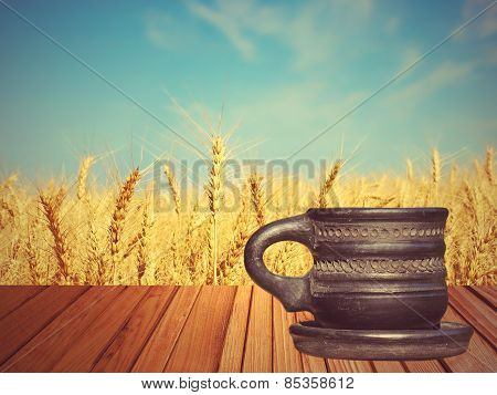 Old Black Tea Mug On Wooden Surface Against Of Golden Wheat.