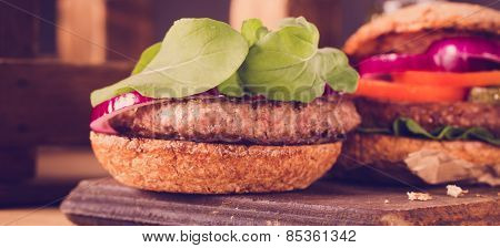 Burger Close Up On A Cutting Board On Wooden Background.
