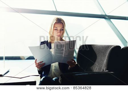 A beautiful young businesswoman holding paperwork sitting new to the big office window