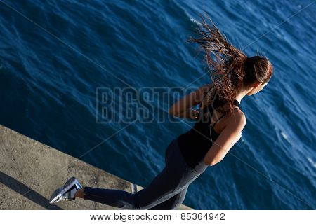 Athletic girl jogging over amazing big waves background at sunny day