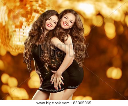 Beautiful Attractive Laughing Two Girls Dancing Over Holiday Discolight Background. Pretty Women Wit