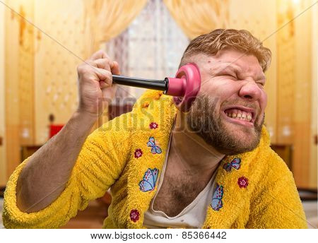 Strange man with a plunger in his ear