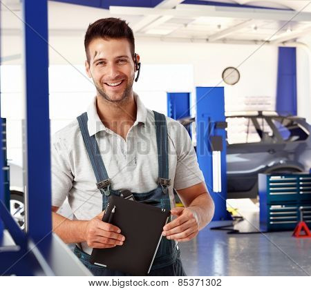 Happy handsome caucasian male car mechanic at auto repair business shop. Wearing workwear clothes and wireless headset, smiling, standing, looking at camera. Greasy, dirty, tablet computer in hand.