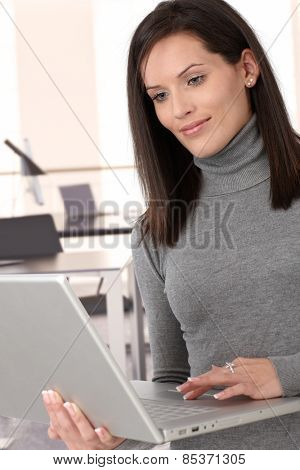 Attractive casual caucasian brunette secretary working with laptop computer
