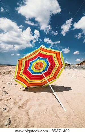 Single colourful umbrella sunny day Aberdovey Wales empty beach